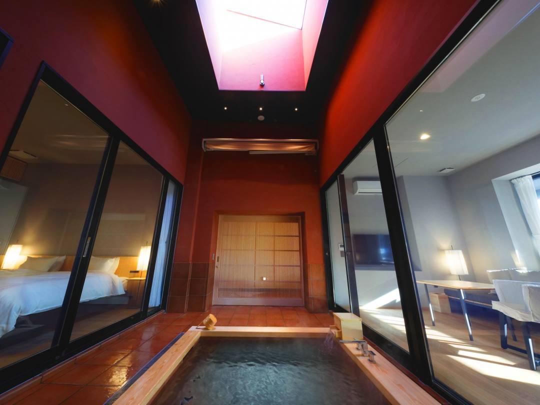 道後温泉 葛城 琴の庭 ガーデンスイート「茜」の温泉は、客室の真ん中に位置しガラス張りという斬新なデザイン。温泉の上には高い天窓がある
